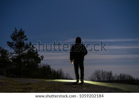 Human standing outdoor at night with flashlight and hoodie on head. Male man standing in Swedish Scandinavian nature and landscape shining with torch. Calm, peaceful photo. Mystical abstract image.