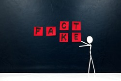 Human stick figure changing word fact to fake. Dark background. Facts versus fake news concept.