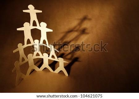 Human team pyramid on brown background