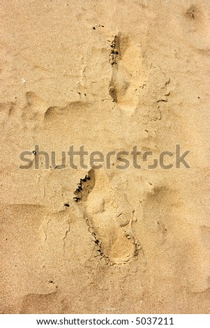 Human trace of a foot on yellow sand