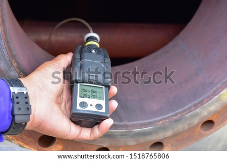Human using the gas detector for detect combustible gas , flammable gas , toxic gas and oxygen depletion in a confined spaces before starting work.