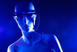 Humanoid robot in neon light. Robot in form of a woman on a dark background. Wire comes out of humanoid robot glasses. Humanoid cyborg as a symbol of artificial intelligence. Cyborg development.