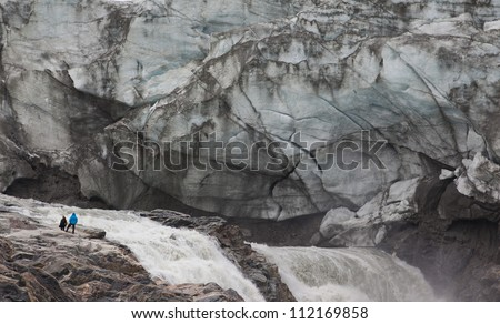 Humans in front of melting glacier, Kangerlussuaq, Greenland