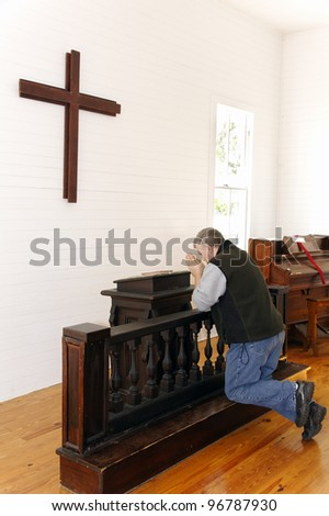 Humble man kneeling and praying in a church with a cross and piano.