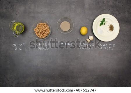 Hummus (Houmous) oriental recipe. Top view of ingredients on kitchen table. Olive oil, chick peas, sesame paste (tahini), lemon, garlic, salt, cumin.