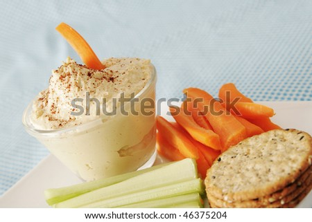 Hummus in a clear bowl with carrot and celery in a white plate