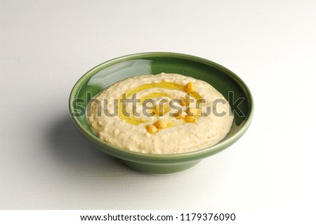 hummus in a green bowl isolated on white background