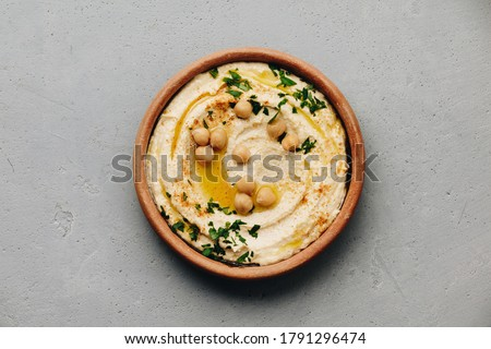 Hummus. Large bowl of homemade hummus garnished with chickpeas, red sweet pepper, parsley and olive oil, flat lay, middle east food ストックフォト ©