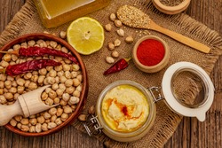 Hummus on old wooden boards background. Dry chickpea, olive oil, lemon, cumin and chili pepper. Traditional food in Middle Eastern and Mediterranean cuisine, top view