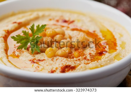 Hummus or houmous, appetizer made of mashed chickpeas dip with tahini, lemon, garlic, olive oil, parsley and paprika on wooden table ストックフォト ©