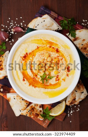 Hummus or houmous, appetizer made of mashed chickpeas dip with tahini, lemon, garlic, olive oil, parsley and paprika on wooden table, top view ストックフォト ©
