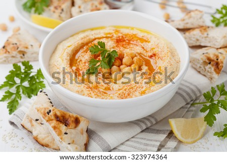 Hummus or houmous, appetizer made of mashed chickpeas with tahini, lemon, garlic, olive oil, parsley and paprika on wooden table ストックフォト ©