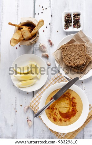 hummus, rye bread and turkish crisps on white distressed table
