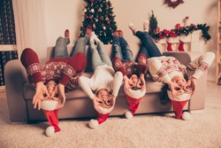Humor, comic, funky funny friendship mode. Four cheerful relatives, married couple, siblings fooling around in knitted traditional costumes, x mas eve celebration, on couch upside down