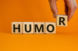 Humor symbol. Wooden cubes with word 'humor'. Male hand. Beautiful orange background. Business and humor concept. Copy space.