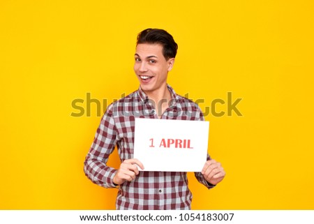 Humorist man holding white table with an inscription 1 april #1054183007