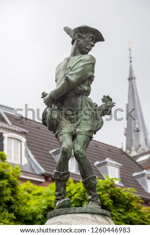Humoristic statue of young man and chicken from a fairy tale on a fontain in the centre of the city of Aken, Germany #1260446983