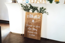 Humorous board about alcohol and love story. White wall background. Wedding day concept.
