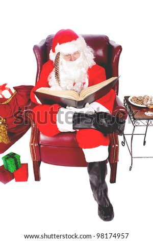 Humorous closeup of Santa Claus (that jolly old elf that  lives at the North Pole) reading and writing in the book of good children
