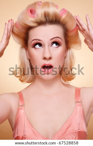 Humorous emotional portrait of beautiful young woman with curlers in hair looking upwards with worried expression
