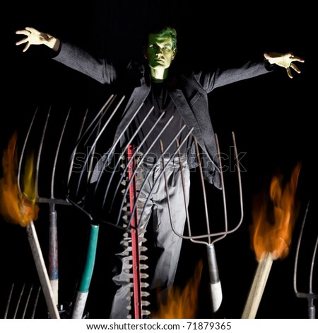 humorous frankenstein setup with pitchforks and flames
