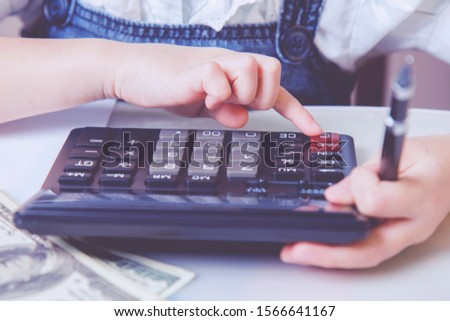 Humorous photo of young business girl calculate US Dollar banknotes money with calculator.