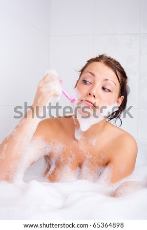 humorous picture of a young brunette woman taking a bath and shaving beard