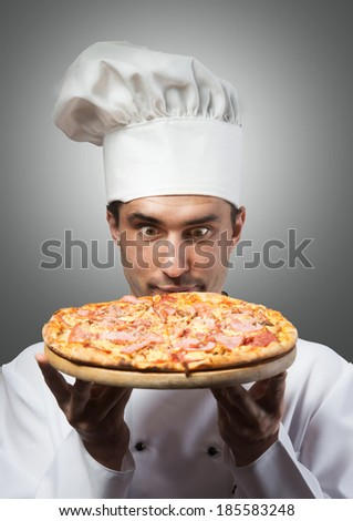 Humorous portrait of a man in chef's hat smelling pizza