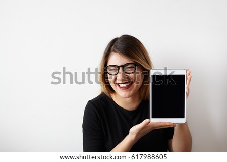 Humorous portrait of attractive young woman in glasses showing blank copy screen tablet, having funny sarcastic face expression, loud laughing meaning gloating, talking