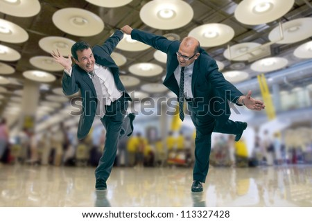 Humorous shot of a pair of running businessmen at the airport