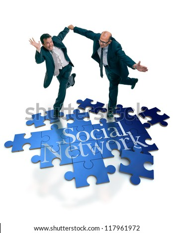 Humorous shot of a pair of running businessmen on a puzzle with the word social network