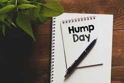 HUMP DAY text written in an office notebook on a wooden table.