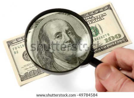Hundred dollar bill under a magnifying glass is being inspected Conceptual photo isolated on white background