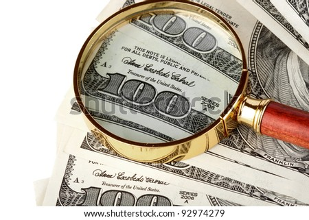 Hundred dollar bill under a magnifying glass  on the white