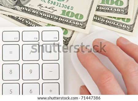 Hundred dollar bills, keyboard calculator and female hand on computer mouse.