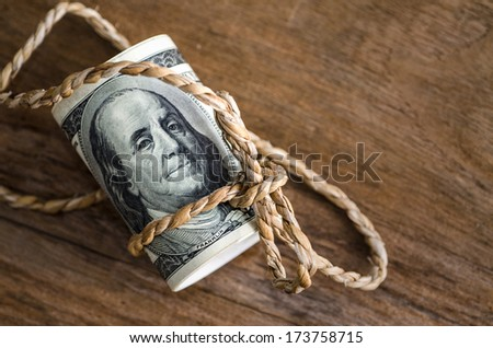 Hundred dollar bills rolled up with  rope on wooden table : copyspace