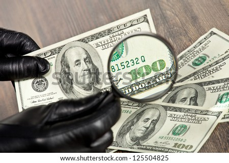 Hundred dollar bills under a magnifying glass are being inspected by man in black gloves