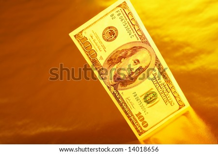 Hundred dollar denomination stands on a reflecting surface of a gold background