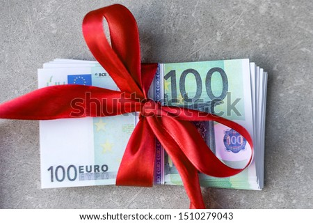 Hundred euro banknotes on a stack with red bow. Gift, bonus or reward concept Foto stock ©