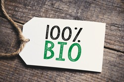 Hundred percent Bio inscription. Green and black inscription hundred percent Bio on blank tags on wooden table