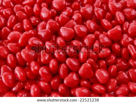 Hundreds of pieces of red candy hearts makes a background for Valentine's Day in February. The hard, red candy is shiny.