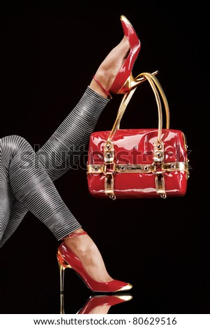 Hung on heel. Stylish red bag hanging on a chic high-heeled shoe.