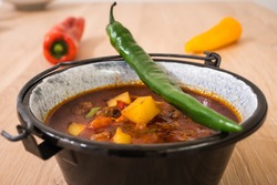 Hungarian Beef Goulash or Gulyas Soup or Stew Served in a Small Cauldron with Potatoes, Meat, Paprika and Chili and Bell Pepper