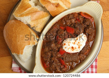 Hungarian goulash beef stew served with crusty bread baguette.