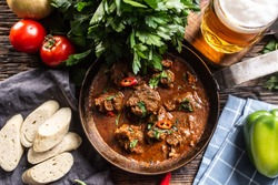 Hungarian goulash in a bowl with bell pepper, tomatoes, herbs, dumplings and a draft beer.