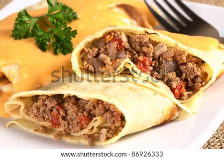 Hungarian-style crepe called Hortobagyi Husos Palacsinta (Crepe a la Hortobagy) filled with meat, tomato and onion amd served with sauce (Selective Focus, Focus on the stuffing in the upper half) Stock fotó ©