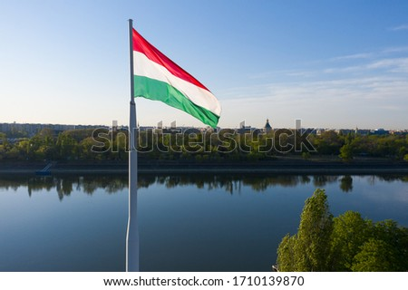 Hungary Budapest. Wind waving a  Hungarian flag. There is the Margit island on the background. Clear sky still river. Stock fotó ©