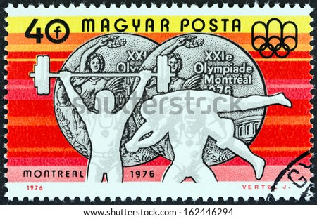 "HUNGARY - CIRCA 1976: A stamp printed in Hungary from the ""Olympic Games, Montreal. Hungarian Medal winners "" issue shows Weightlifting and Wrestling (silver medals), circa 1976.  #162446294"