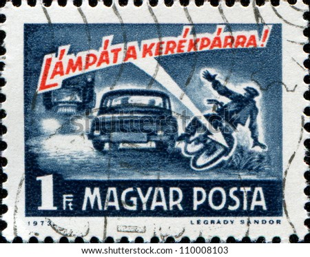 "HUNGARY - CIRCA 1973: A stamp printed in Hungary from the ""Road Safety"" issue shows a car running down cyclist and ""Cyclist use a lamp !"" inscription, circa 1973"