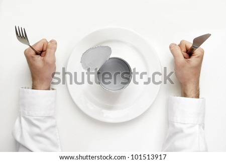 Hunger concept. Empty tin with human hands holding fork and knife from top view. - stock photo